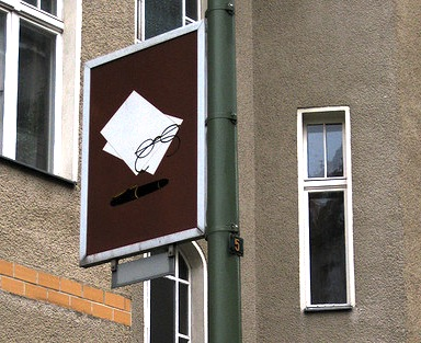 A street sign with an image of a pair of glasses and a piece of paper with typewriting on it.
