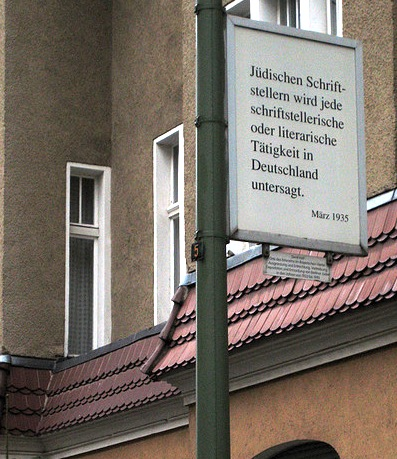 A street sign with german writing on it explaining that Jewish authors are no longer allowed to write as of March 1935.