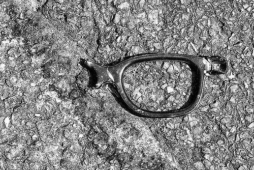 A broken pair of glasses on a patch of rough pavement.